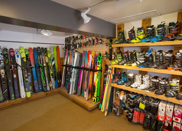 Skis, boots, bindings, socks, and rentals on display in equipment rental shop.